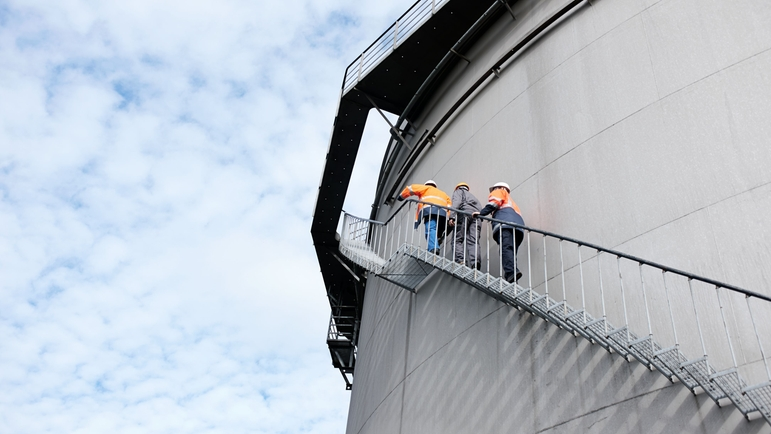 Three men are climbing the stairs around an oil tank, landscape view